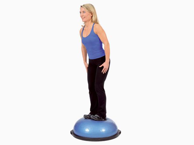 Frau in Endstellung der Übung Stand mit Gewichtsverlagerung für den Bosu