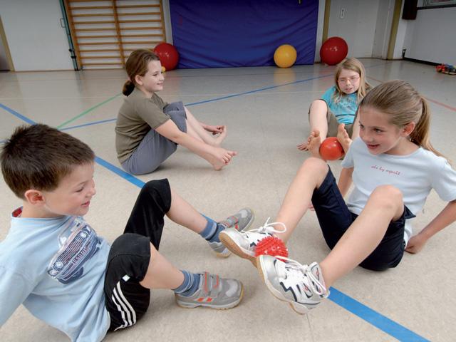 Kinder in Ausgangsstellung der Übung Käfer für den TheraBand Soft Weights
