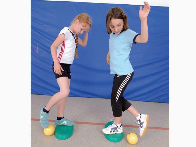 Kinder in Ausgangsstellung der Übung Rollen für den Balance- und Stabilitätstrainer