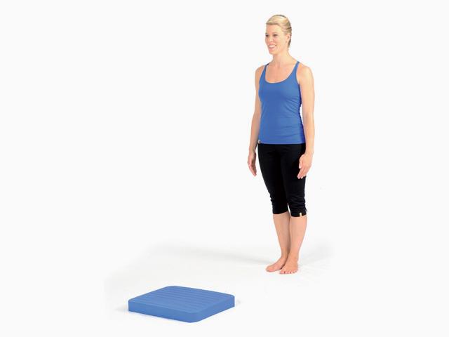 Frau in Ausgangsstellung der Übung Schritte für den Balance- und Stabilitätstrainer