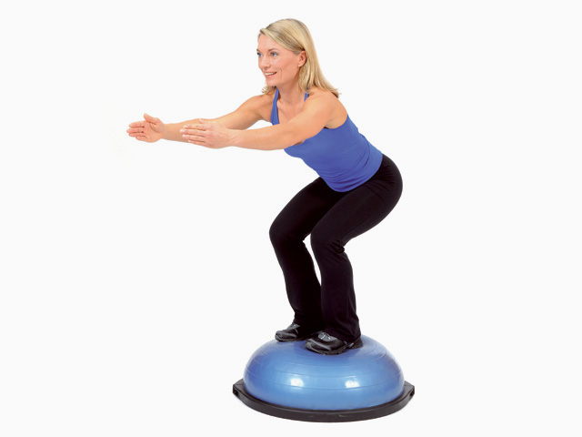 Frau in Zwischenstellungg der Übung Squat und Seit-Schritt mit Kniebeuge für den Bosu