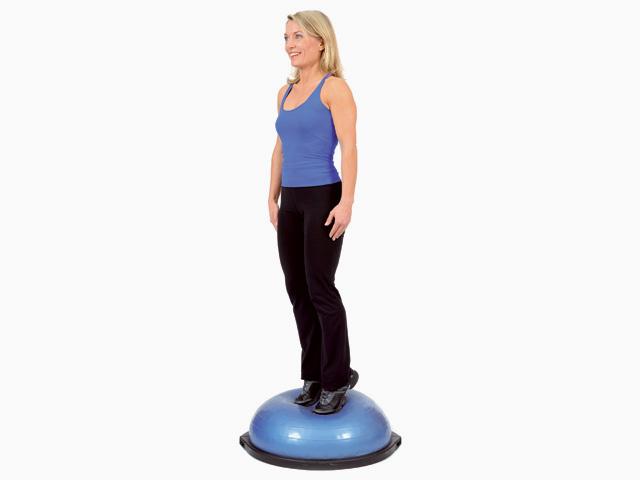 Frau in Zwischenstellungg der Übung Stand mit Gewichtsverlagerung für den Bosu