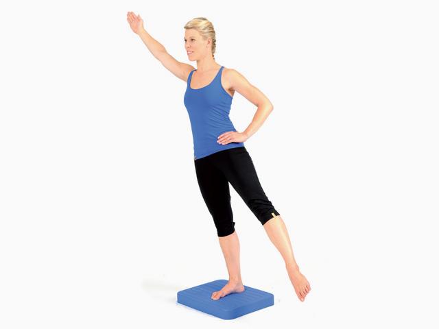 Frau in Endstellung der Übung Diagonale Streckung für den Balance- und Stabilitätstrainer