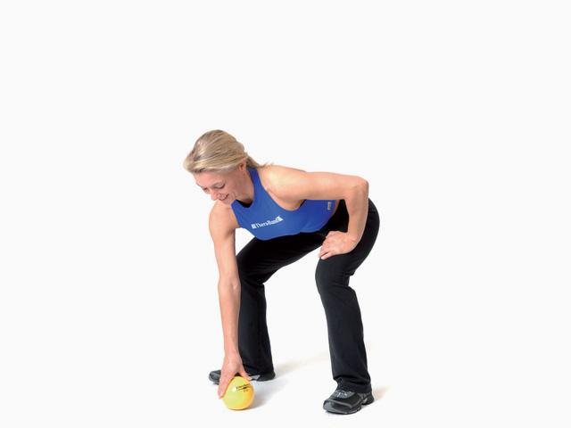 Frau in Zwischenstellung der Übung Bücken und Strecken für den TheraBand Soft Weights