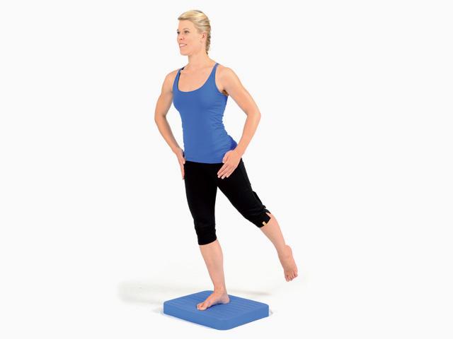 Frau in Endstellung der Übung Schrittstellung (weit oder eng) für den Balance- und Stabilitätstrainer
