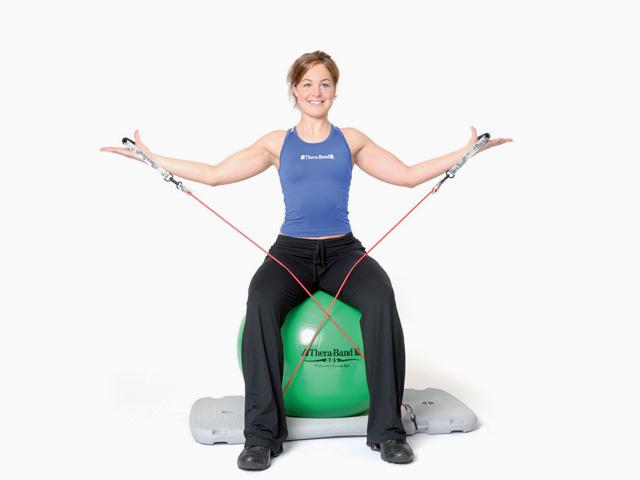 Frau in Variante der Übung Armseitheben für den Balance- und Stabilitätstrainer