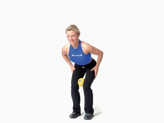 Frau in Endstellung der Übung Kniebeuge für den TheraBand Soft Weights
