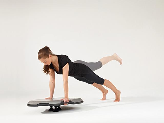 Frau in Ausgangsstellung der Übung Balancierender Beinheber für den Balance- und Stabilitätstrainer