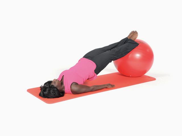 Frau in Zwischenstellung der Übung Brücke mit langen Beinen / Shoulder bridge für den Gymnastikball