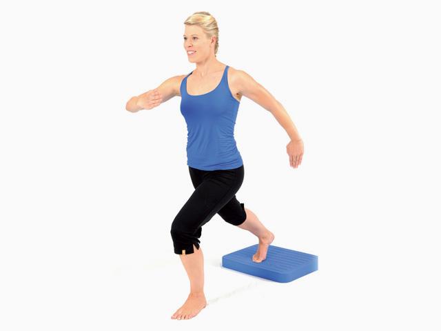 Frau in Endstellung der Übung Schritte für den Balance- und Stabilitätstrainer