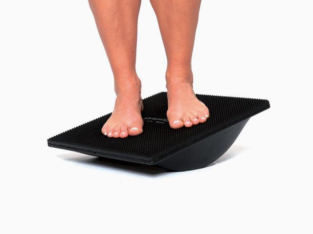 Frau in Endstellung der Übung Stand auf dem Kippbrett mit verschiedenen Fußpositionen für den Balance- und Stabilitätstrainer