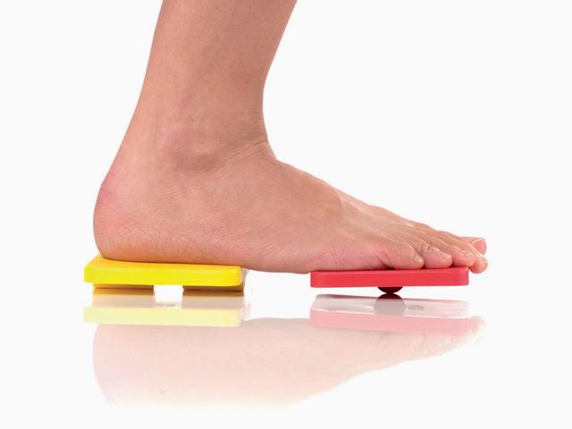 Frau in Zwischenstellung der Übung Bein heben für den Balance- und Stabilitätstrainer