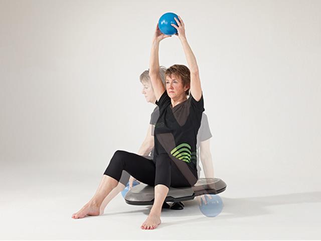 Frau in Ausgangsstellung der Übung Ball ablegen (seitlich) für den Balance- und Stabilitätstrainer