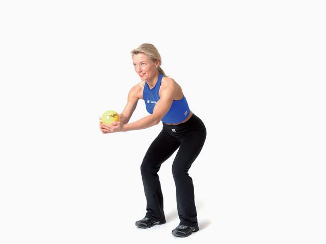 Frau in Endstellung der Übung Kniebeuge mit Armvorheben für den TheraBand Soft Weights