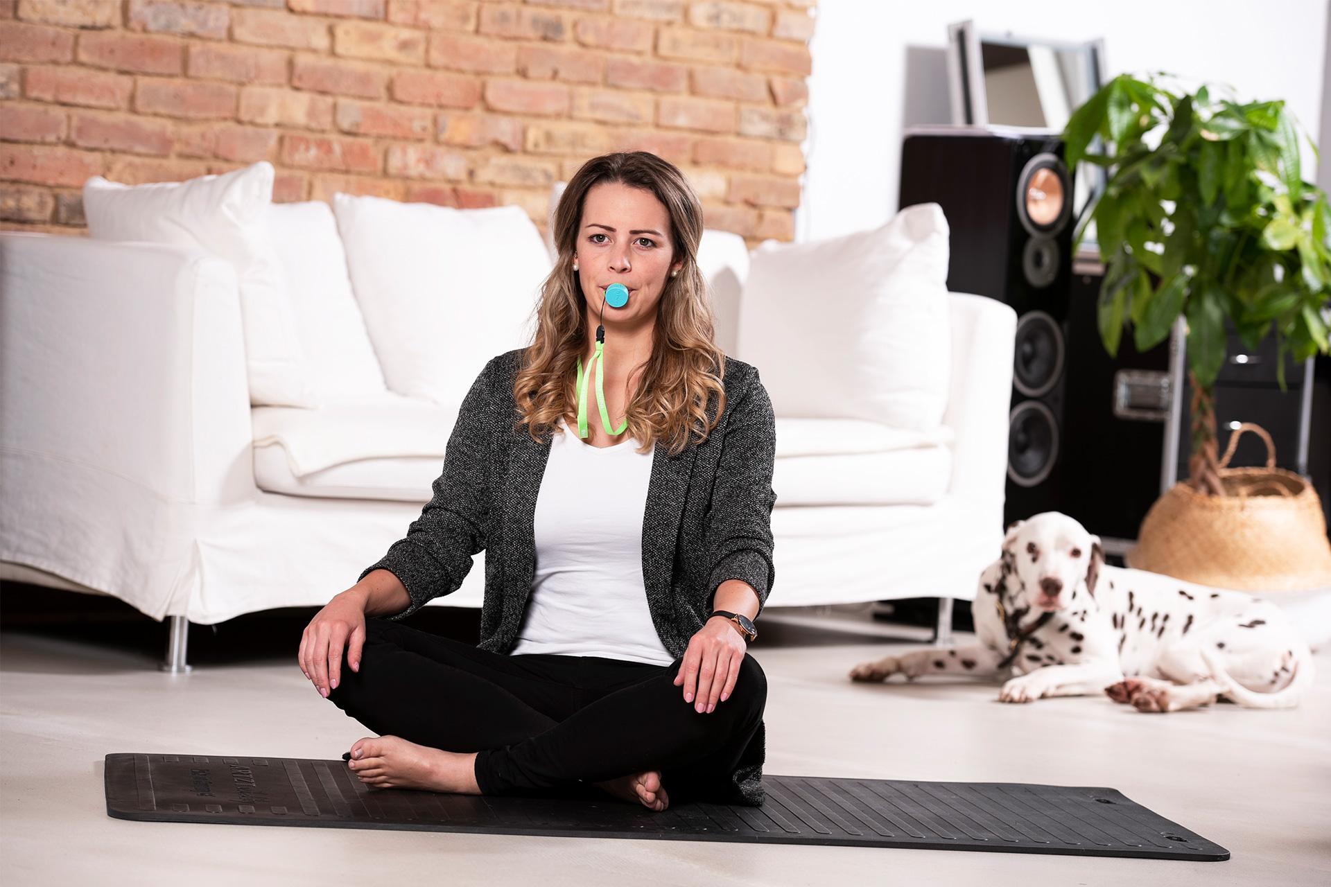 Frau im Schneidersitz verwendet den Relaxator