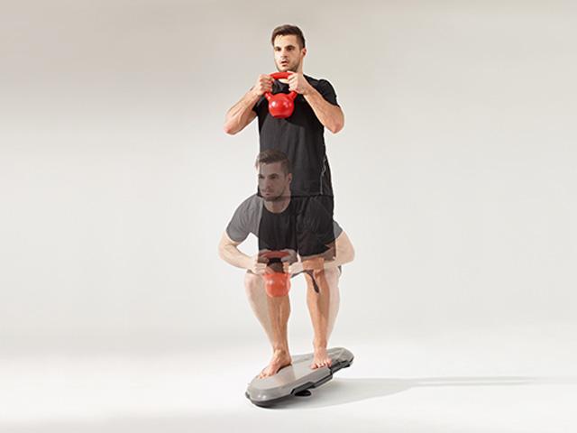 Mann in Ausgangsstellung der Übung Squat mit Kettlebell für den Balance- und Stabilitätstrainer