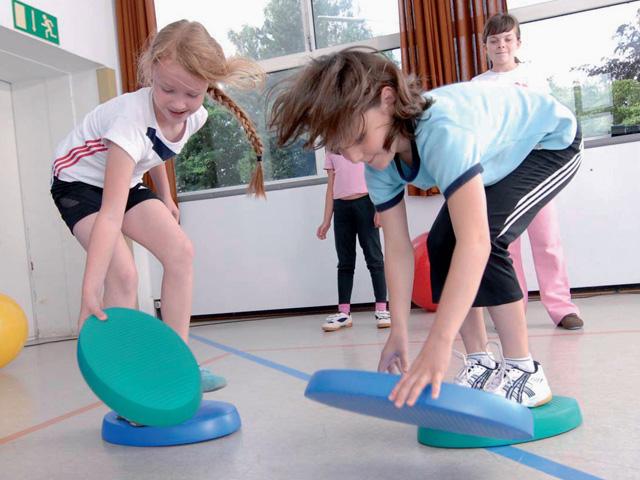Kinder in Ausgangsstellung der Übung Flussüberquerung für den Balance- und Stabilitätstrainer