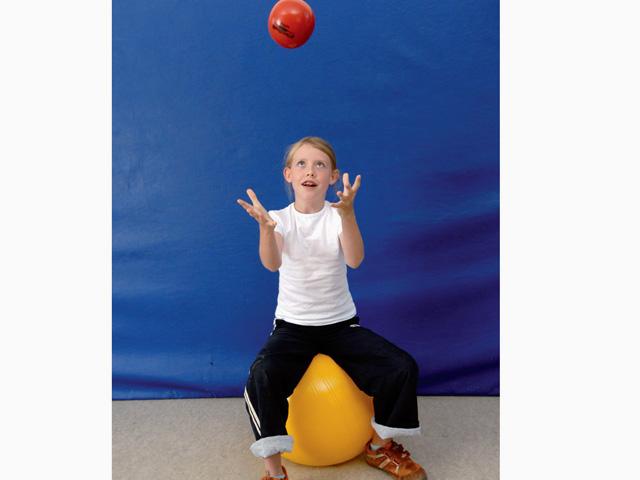 Kinder in Ausgangsstellung der Übung Nuss werfen für den TheraBand Soft Weights