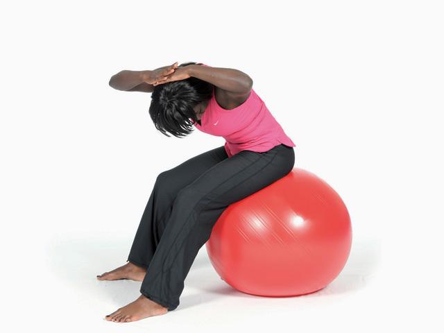 Frau in Zwischenstellung der Übung Wellenbewegung mit Rotation / Twisted spine wave für den Gymnastikball
