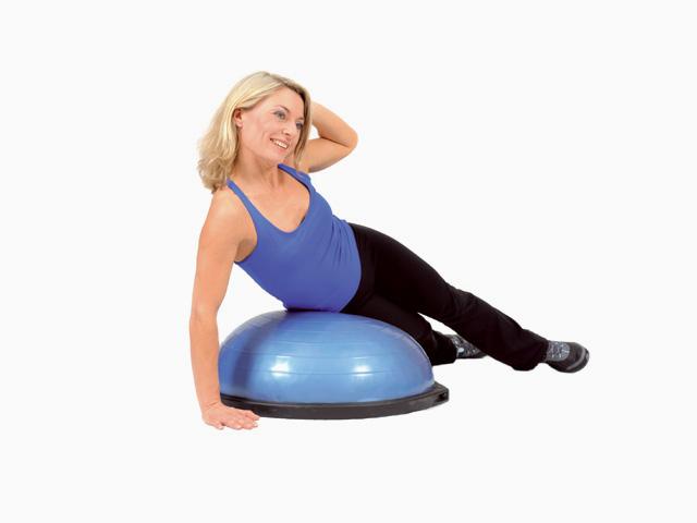 Frau in Zwischenstellung der Übung Oberkörperflexion für den Bosu