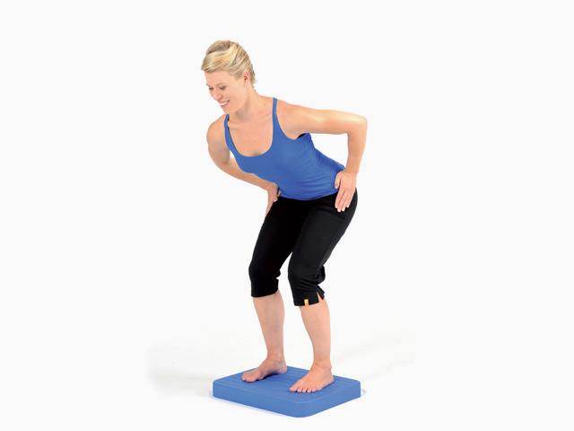 Frau in Endstellung der Übung Parallelstand mit Kniebeuge für den Balance- und Stabilitätstrainer