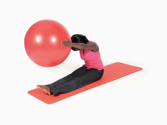 Frau in Zwischenstellung 2 der Übung Auf- und abrollen / Roll up and down für für den Gymnastikball