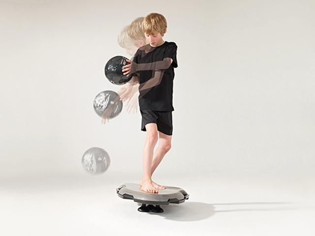Junge in Ausgangsstellung der Übung Ball prellen rund 180° um das Board für den Balance- und Stabilitätstrainer