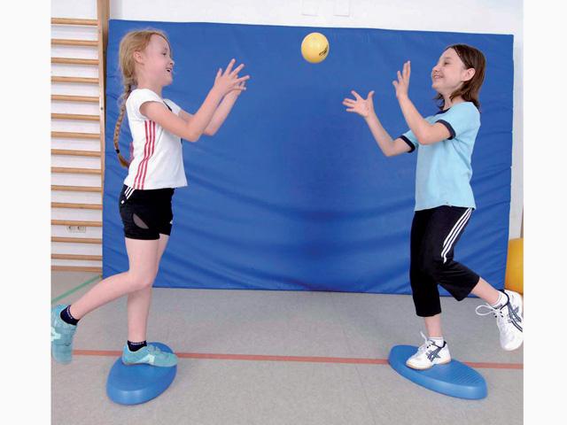 Kinder in Ausgangsstellung der Übung Werfen und Fangen für den Balance- und Stabilitätstrainer
