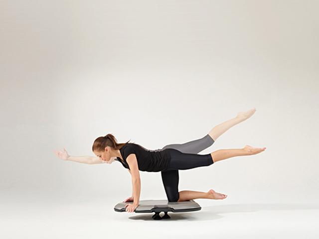 Frau in Ausgangsstellung der Übung Vierfüßlerstand für den Balance- und Stabilitätstrainer