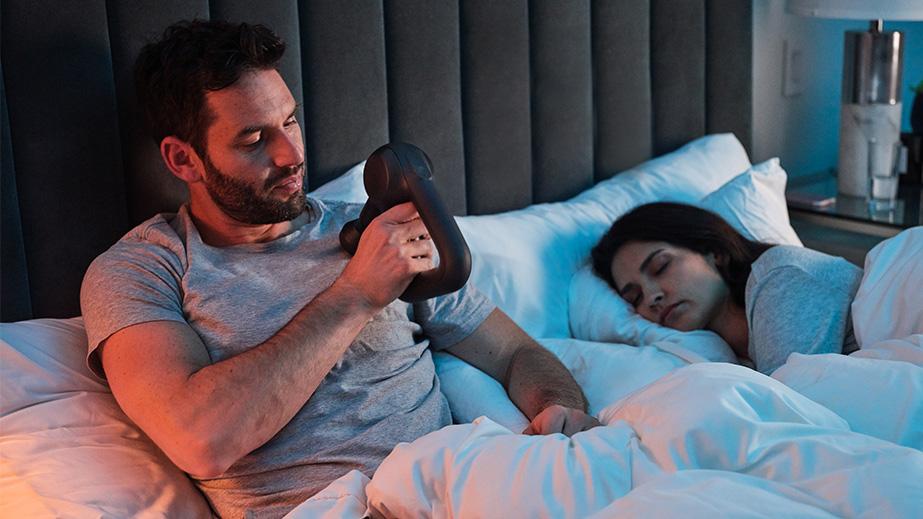 Mann liegt im Bett und behandelt seine Schulter mit der neuen Theragun PRIME.
