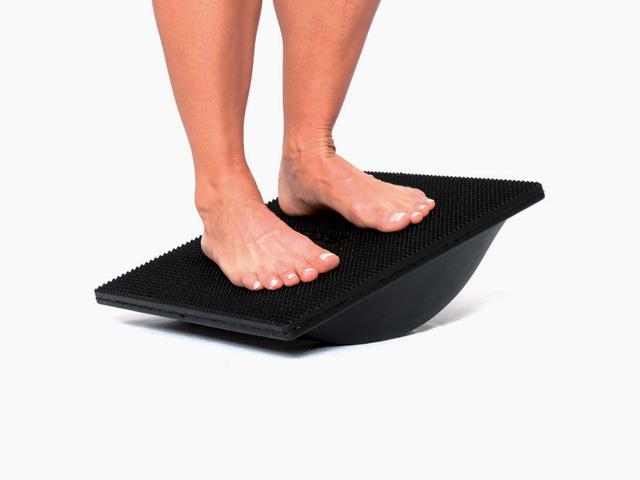 Frau in Zwischenstellung der Übung Stand auf dem Kippbrett mit verschiedenen Fußpositionen für den Balance- und Stabilitätstrainer