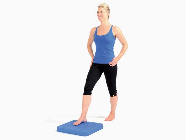 Frau in Ausgangsstellung der Übung Schrittstellung (weit oder eng) für den Balance- und Stabilitätstrainer