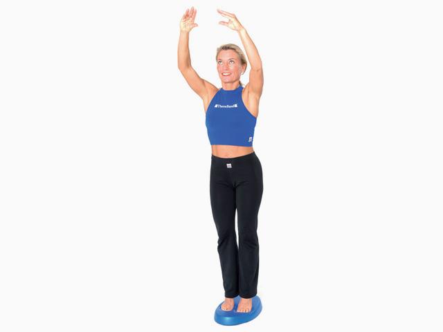 Frau in Endstellung der Übung Stand auf dem Stabilitätstrainer für den Balance- und Stabilitätstrainer