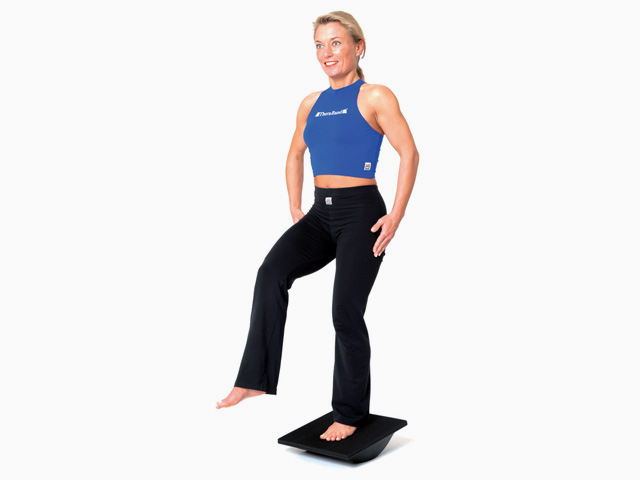 Frau in Endstellung der Übung Stand auf dem Kippbrett (Sagitalebene) für den Balance- und Stabilitätstrainer