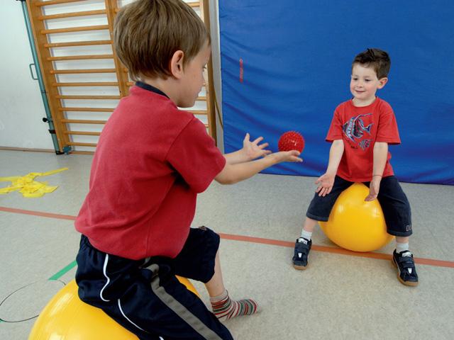 Kinder in Endstellung der Übung Nuss werfen für den TheraBand Soft Weights