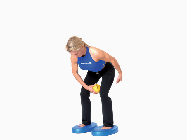 Frau in Variante der Übung Bein heben für den Balance- und Stabilitätstrainer